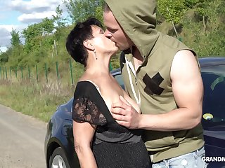Perverted short haired mature brunette stands at bottom knees to give BJ outdoors